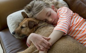 A young girl cuddling with her furry pet.