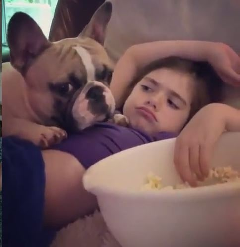 A girl eating popcorn with Frenchie Pug