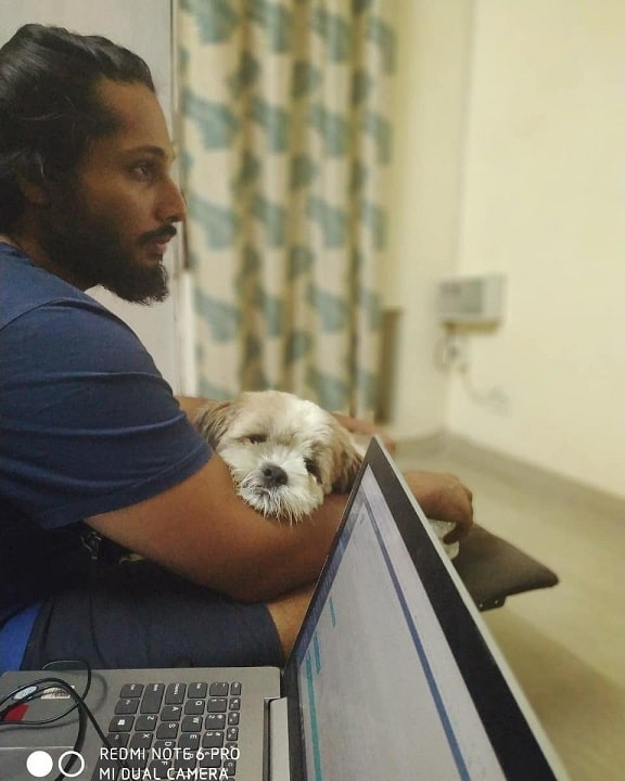 Cavachon cuddling with its master
