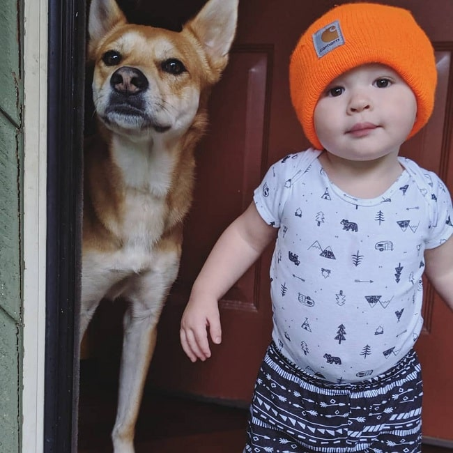 A cute baby and Dingo posing for a pic