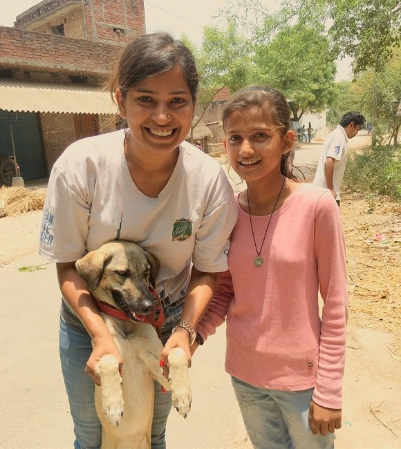 A girl and a lady playing with a Indian Pariah Dog