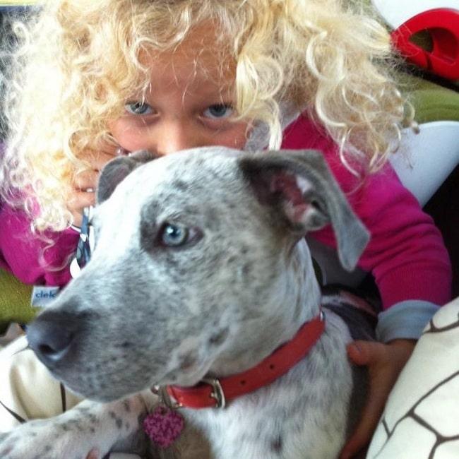 A girl and a Catahoula Bulldog puppy cuddling