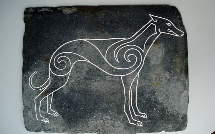 A picture of an ancient Celtic Hound crafted in a stone.